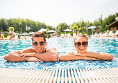 Young couple relaxing in resort swimming pool.