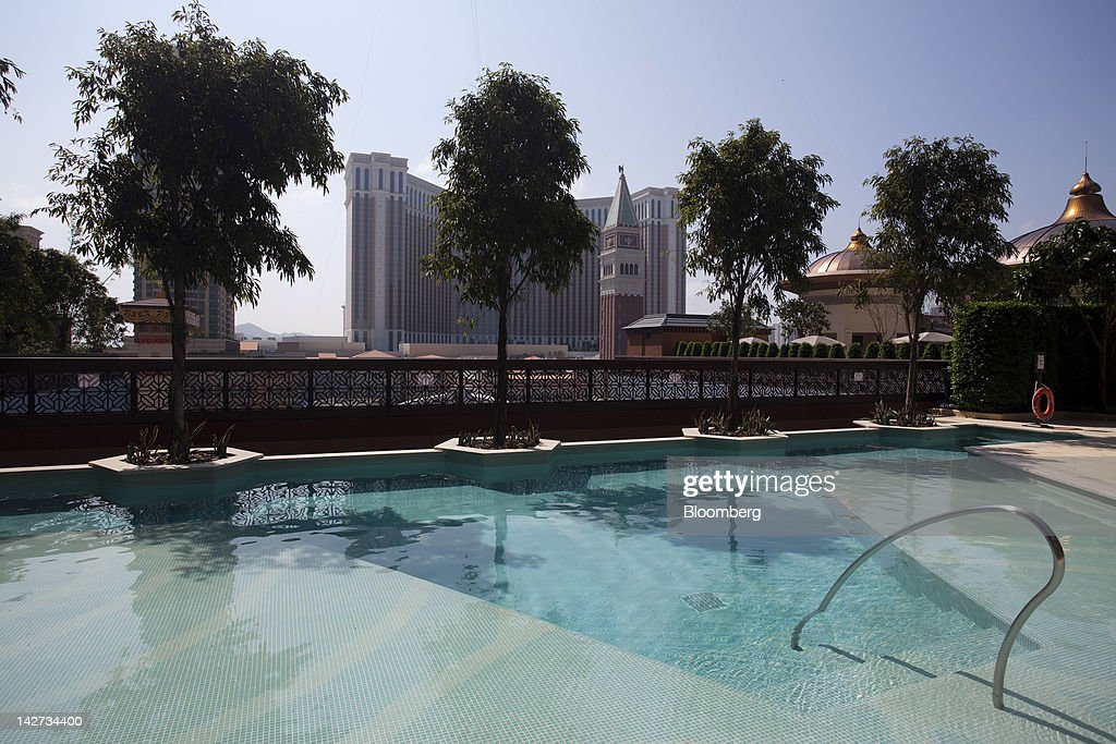 A swimming pool shared by the Conrad Macao and Holiday Inn Macao hotels sits overlooking the the Venetian Macau resort and casino, center, in Macau, China, on Wednesday, April 11, 2012. Las Vegas Sands Corp. Chairman Sheldon Adelson plans to spend $35 billion on building Spanish gambling resorts over nine years and will add a new Macau location to expand globally. Photographer: Jerome Favre/Bloomberg via Getty Images
