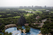 A swimming pool sits near the golf course and residential properties at Mission Hills Resort Haikou in Haikou Hainan Province China on Saturday April...
