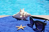 Swimming pool sunglasses towel starfish and shell