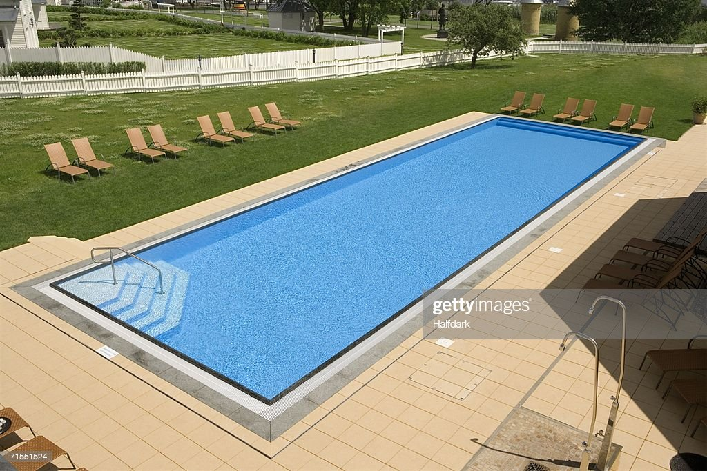 A swimming pool surrounded by lounge chairs