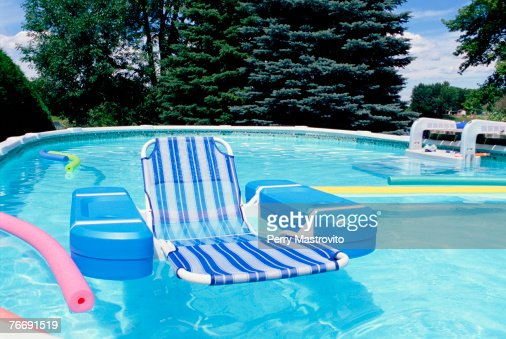 Swimming pool with floating lounge chair stock photo - Swimming pool floating lounge chairs ...