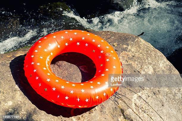 Swimming tube on stone near river