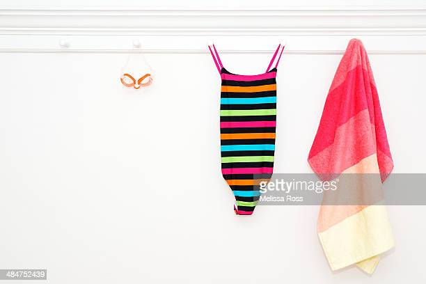 Swimsuit, goggles and beach towel hung from pegs