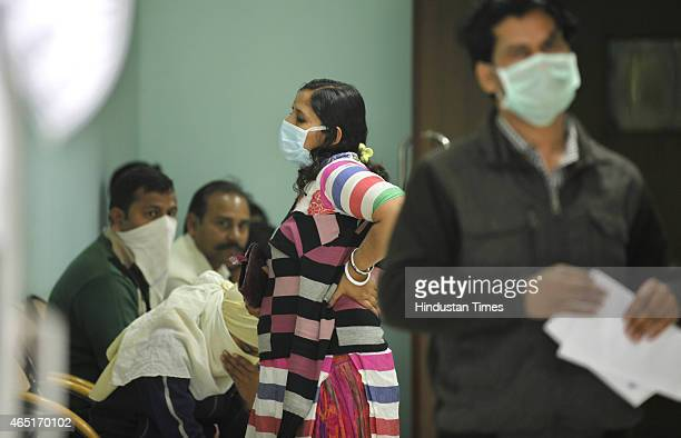 Swine flu suspect patients wait outside swine flu screening centre at the Ram Manohar Lohia Hospital on March 3 2015 in New Delhi India According to...