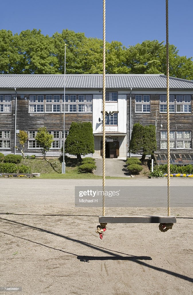 Swing in playground outside school : Stock Photo