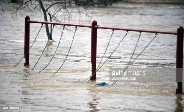 A swing set sways from rushing water at Riverbend Park as the Oroville Dam releases water down the spillway in Oroville California on February 13...