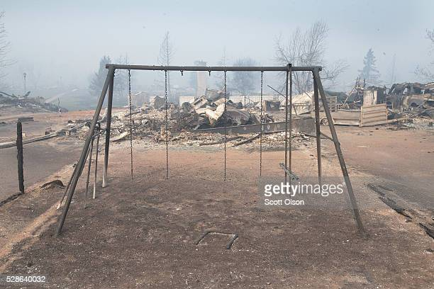 A swing set with the swings burned away sits in a residential neighborhood destroyed by a wildfire on May 6 2016 in Fort McMurray Alberta Canada...