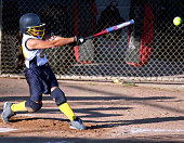 Powerful fastpitch softball swing, with ball flying off the bat.