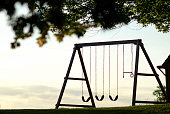 A wooden swings is backlit by a late evening sky framed by leaves in the foreground.