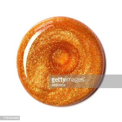 Swirl of orange nail polish, overhead view