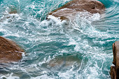 Strong sea current creating foamy surface and swirling water motion among rocks at high tide