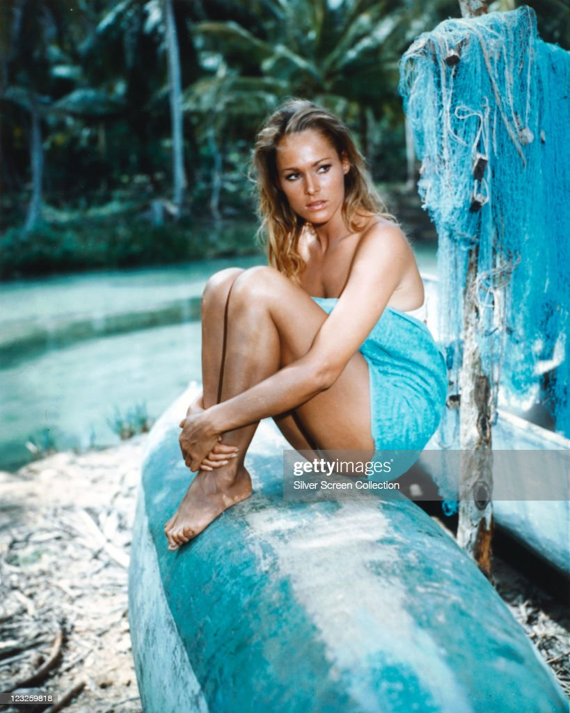 Ursula Andress, Swiss actress, wrapped in a blue towel, sitting on the hull of an upturned boat, with blue fishing nets hanging to the right of the image, circa 1955.