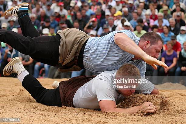 Swiss Alpine wrestler Adrian Laimbacher fights on top of Hanspeter Luginbuehl during the Alpine Wrestling Festival BruenigSchwinget at the top of the...