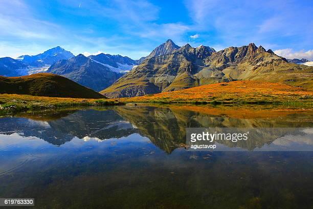 Swiss alps, lake reflection, golden autumn alpine meadow, Zermatt