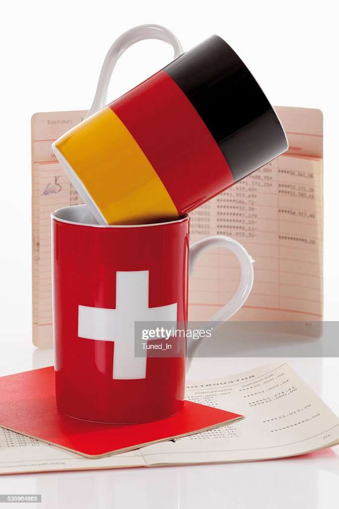 Swiss and german flag cups with bank book : Stock Photo