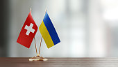 Swiss and Ukrainian flag pair on desk over defocused background. Horizontal composition with copy space and selective focus.