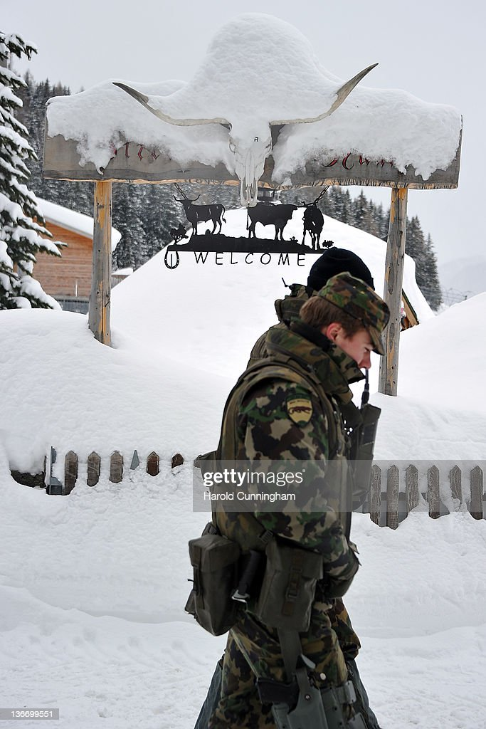 Swiss army soldiers walk past a welcome sign featuring cows and an animal skull on January 10, 2012 in Davos, Switzerland. The World Economic Forum, which gathers the World's top leaders, runs from January 25 - 29.