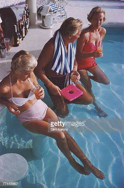 Swiss bandleader and restaurateur Teddy Stauffer with Dorothy Webb and Mrs Charles Rogers in the pool at the Villa Vera Spa Racquet Club pool...