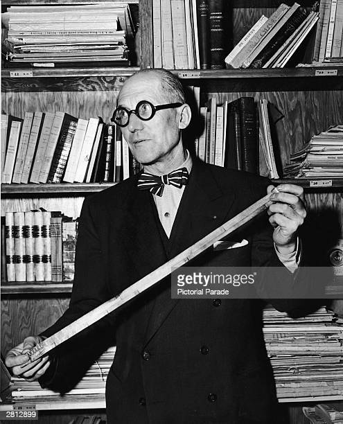 Swiss born architect Le Corbusier stands in an office holding a modular measuring device New York City circa 1950