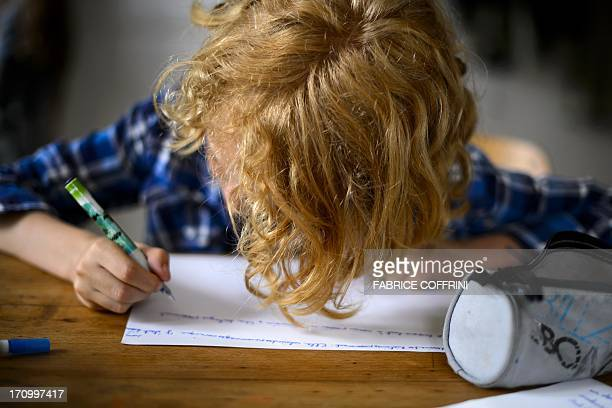 Swiss boy Leon does his homework on June 20 2013 in his home in Moudon western Switzerland USE