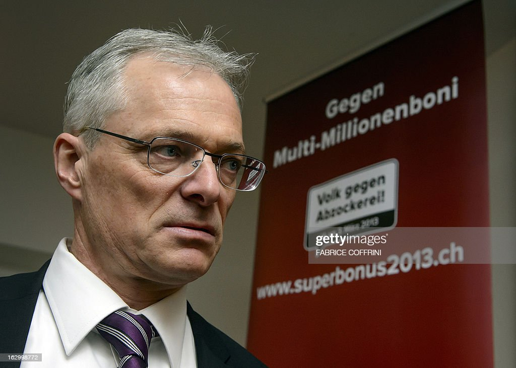 Swiss businessman and senator Thomas Minder looks on next to a banner waiting for the result on a nationwide vote on March 3, 2013 in Schaffhausen. Switzerland took part in a popular vote on whether to rein in executive pay and force business leaders to give up departure compensation known as golden parachutes.
