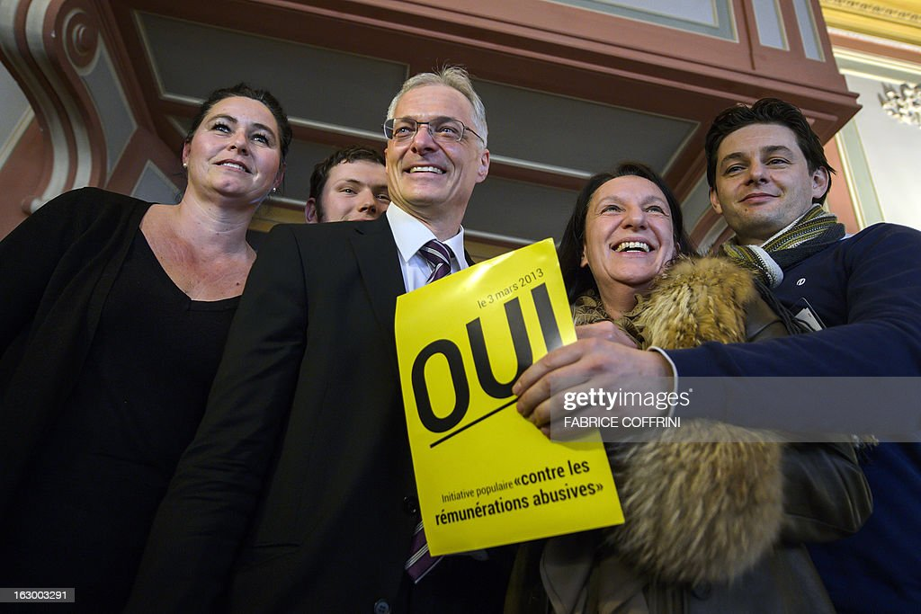 Swiss businessman and senator Thomas Minder (3rdR) pose on March 3, 2013 with members of the support committee behind a poster reading 'Yes' in French while waiting for the result of a nationwide vote in Schaffhausen. Switzerland took part in a popular vote on whether to rein in executive pay and force business leaders to give up departure compensation known as golden parachutes. The so-called Minder Initiative, after its sponsor businessman and senator Thomas Minder, already passed with 67.4 percent of votes in favour in Geneva, where voting ended at noon.