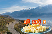 Swiss cheese and flag composite with Alps background