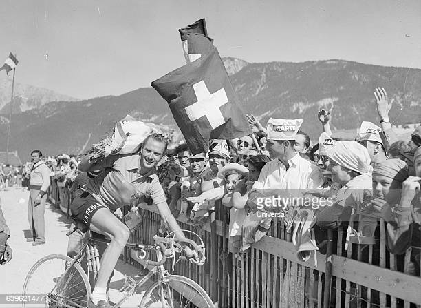 Swiss cyclist Hugo Koblet poses with the leading yellow shirt next to a crowd of fans He is in the 19th stage of the 1951 Tour de France | Location...