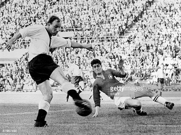 Swiss defender Heinz Schneiter attempts to block the shot of German forward Uwe Seeler 03 June 1962 in Santiago during the World Cup first round...