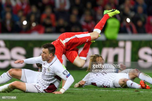 Swiss defender Stephan Lichtsteiner falls between Latvian midfielder Vitalijs Jagodinskis and Latvian defender Kaspars Gorkss during the WC 2018...