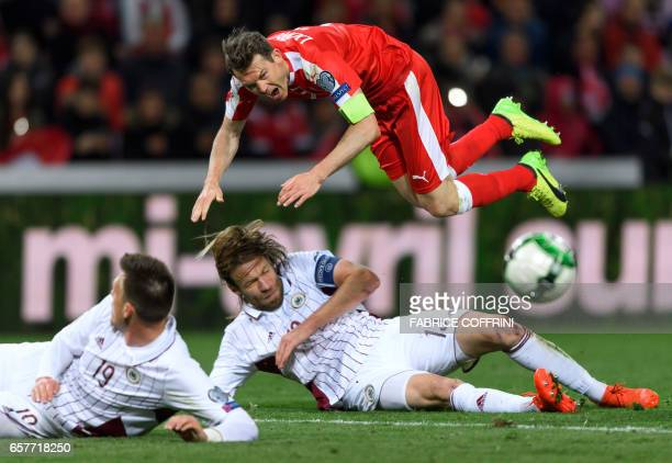 Swiss defender Stephan Lichtsteiner falls over Latvian defender Kaspars Gorkss during the FIFA World Cup 2018 qualifying football match between...