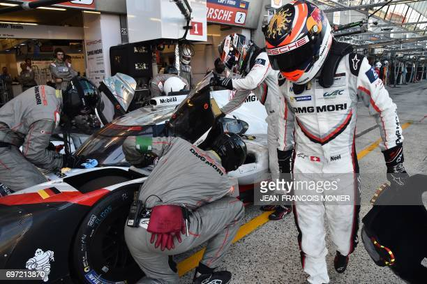 Swiss' driver Neel Jani leaves his Porsche 919 Hybrid N°1 and gives a relay to England's driver NickTandy during the 85th Le Mans 24hours endurance...