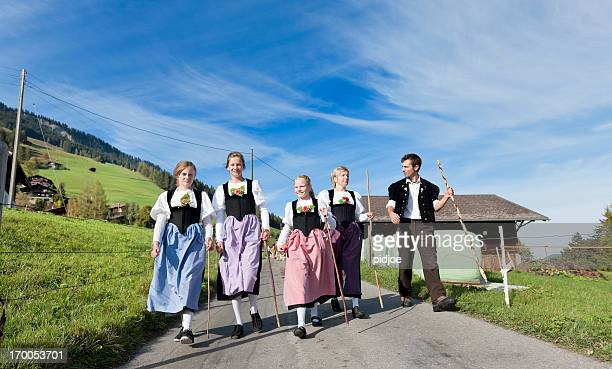 Swiss farmer family in traditional clothing walking down mountain