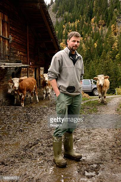 Swiss Farmer Stands on Farm with Cows in Mountains