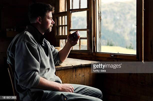 Schweizer farmer mit seinem Kaffee am Morgen vor Alpen