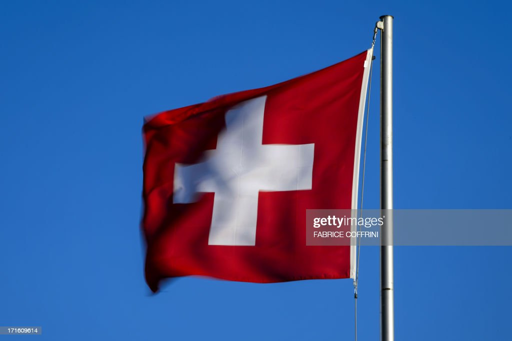 A Swiss flag flies at sunrise on June 26, 2013 in the city of Versoix near Geneva.