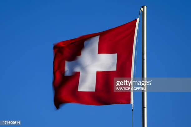 A Swiss flag flies at sunrise on June 26 2013 in the city of Versoix near Geneva AFP PHOTO / FABRICE COFFRINI
