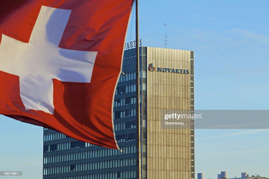 A Swiss flag flies near the headquarters of Novartis AG in Basel, Switzerland, on Wednesday, Jan. 29, 2014. Novartis AG, Europe's biggest drugmaker by sales, said fourth-quarter profit fell as currencies in emerging markets weakened against the dollar. Photographer: Gianluca Colla/Bloomberg via Getty Images