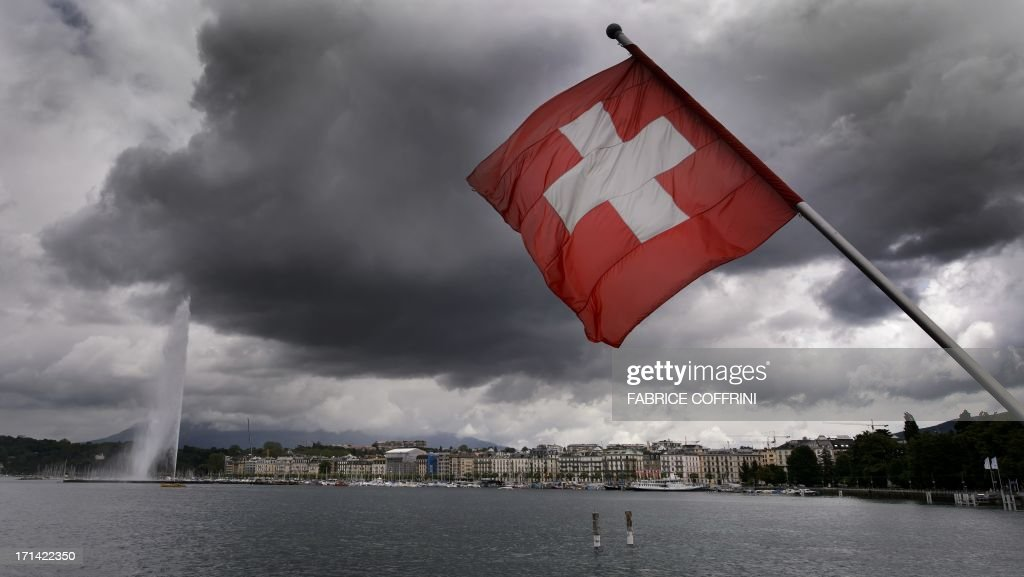 A Swiss flag flies on the shores of Geneva Lake in front of the Geneva Fountain (L) on June 14, 2013 in the center of Geneva.