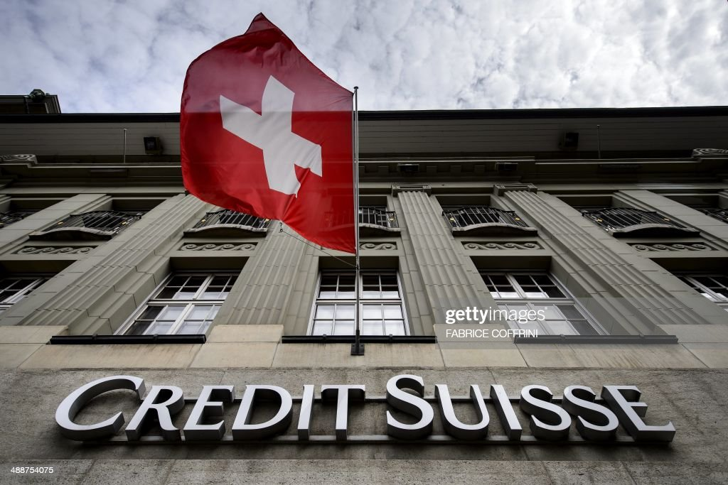 A Swiss flag flies over a sign of Swiss bank Credit Suisse on May 8, 2014 in Bern. A senior US official told AFP on May 5, 2014 that the probe of Credit Suisse's past practice of helping its wealthy US clients evade taxes by sheltering their funds abroad was almost complete and that criminal charges could be brought within 'a few weeks.'.