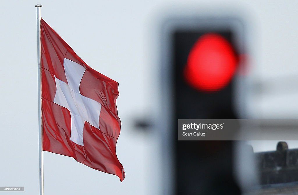 A Swiss flag flies over the Swiss Embassy near a red traffic light on February 10, 2014 at Berlin, Germany. Swiss citizens voted with a narrow majority in favour of measures to curb immigration from countries including from the European Union in a move that will require Swiss officials to renegotiate up to seven bilateral treaties with the EU. The referendum was launched by the right-wing Swiss People's Party (SVP). Approximately one quarter of people living in Switzerland are foreigners.