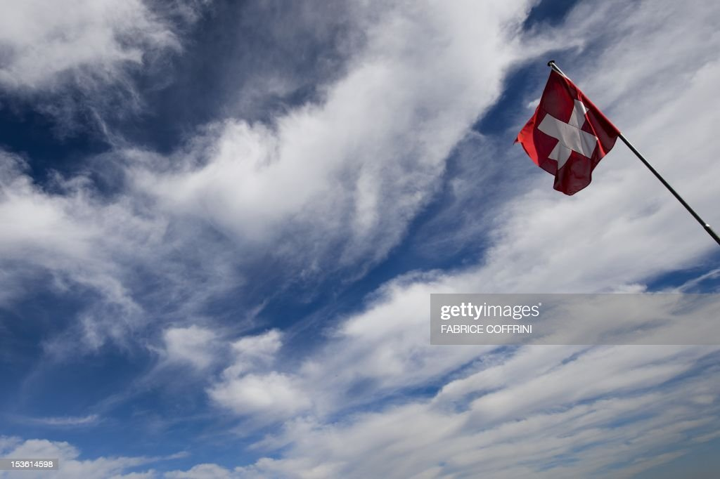 Swiss flag floats in the sky at 1,989 meters high Stanserhorn mountain, Central Switzerland on October 6, 2012. AFP PHOTO / FABRICE COFFRINI