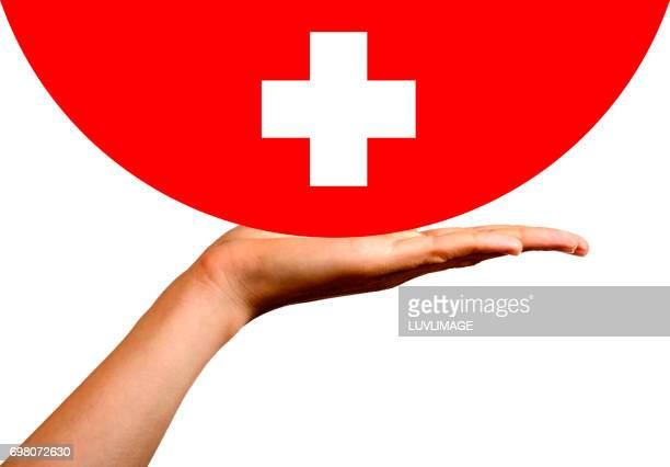 Swiss flag in a hemisphere, on an open hand.