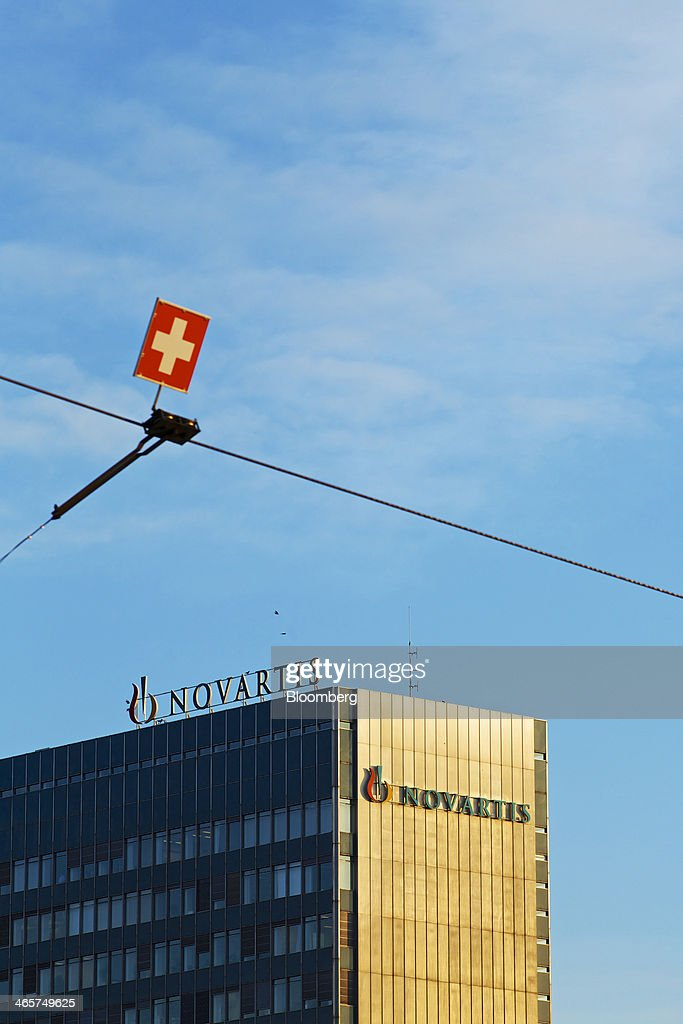 A Swiss flag logo sits near the headquarters of Novartis AG in Basel, Switzerland, on Wednesday, Jan. 29, 2014. Novartis AG, Europe's biggest drugmaker by sales, said fourth-quarter profit fell as currencies in emerging markets weakened against the dollar. Photographer: Gianluca Colla/Bloomberg via Getty Images