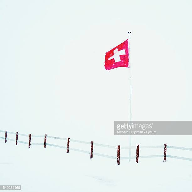 Swiss Flag On Snowy Landscape Against Clear Sky