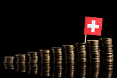 Swiss flag with lot of coins isolated on black background
