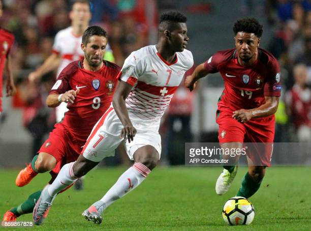 Swiss forward Breel Embolo vies with Portugals midfielder Joao Moutinho and defender Eliseu vie during the FIFA World Cup 2018 Group B qualifier...