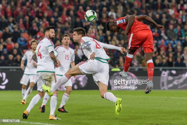 Swiss foward Breel Embolo heads the ball next to Hungarian defender Barnabas Bese during the FIFA World Cup WC 2018 football qualifier match between...