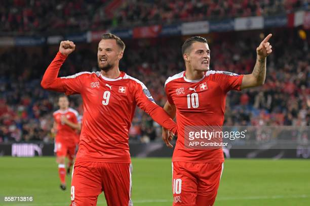Swiss foward Haris Seferovic and his teammate midfielder Granit Xhaka celebrate a goal during the FIFA World Cup WC 2018 football qualifier match...